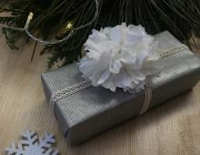 Srebrny papier ozdobiony został wykonanym ręcznie białym kwiatem z bibuły