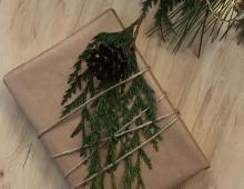 Szary papier przykryty zieloną gałązką i szyszką - to idealne opakowanie dla lubiących styl eko.
